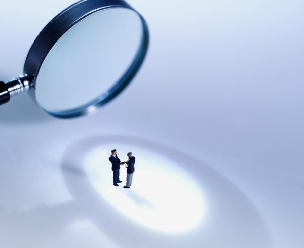 Close-up of magnifying glass focusing on two people --- Image by © Royalty-Free/Corbis